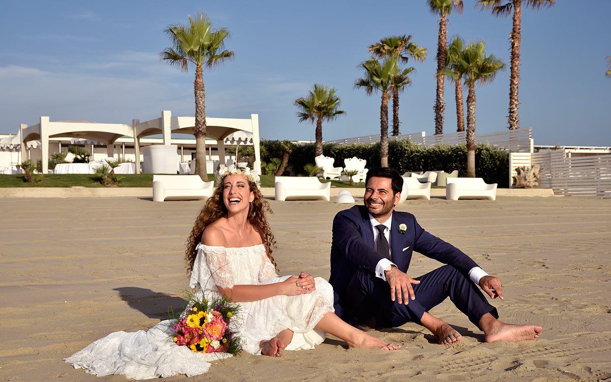 Sposa seduta in spiaggia con corona di fiori